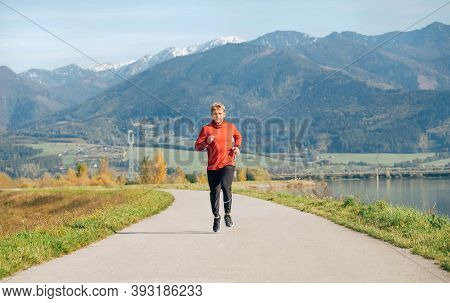 Man Dressed In Red Long Sleeve Shirt Running By The Asphalt Road With Mountain Background. Sporty Pe