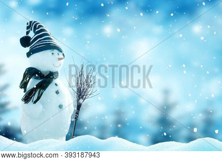 Merry Christmas and happy New Year greeting card with copy-space. Happy snowman with a broom  standing in Christmas landscape. Snow background. Winter fairytale.
