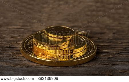 A Few Gold Coins Fineness 999.9 On A Background Of Rough Wood Texture.