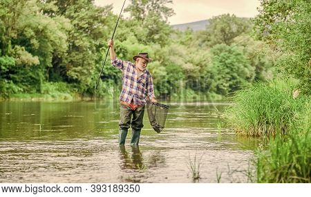 Retirement. Mature Man Fly Fishing. Man Catching Fish. Fisherman With Fishing Rod. Hobby And Sport A