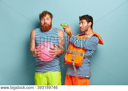 Insecure Bearded Man With Foxy Hair, Holds Ball Plays Water Game With Friend. Serious Guy Wears Life