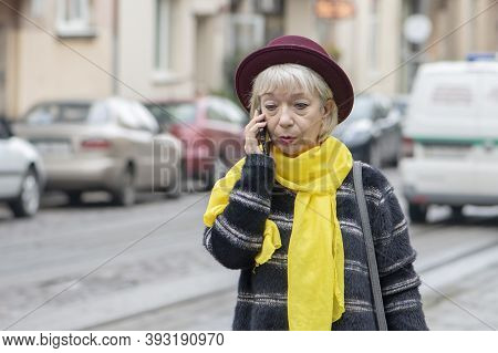 An Elderly Woman 60-65 Years Old In A Medical Mask Is Talking On The Phone And Looks Very Confused.