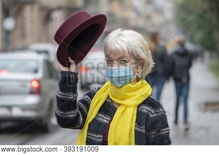 An Elderly Woman Of 60-65 Years Old Holds A Hat In The Background Of The City Landscape. Concept: Re