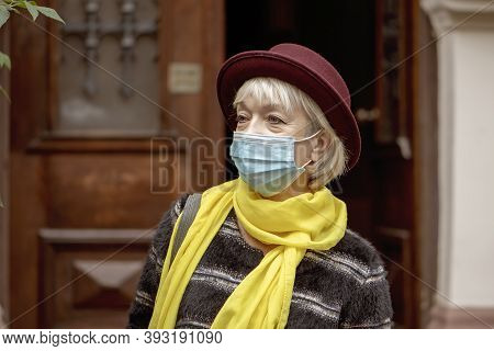 An Elderly Woman 60-65 Years Old In A Medical Mask Comes Out Of The Entrance Of An Old House. Concep