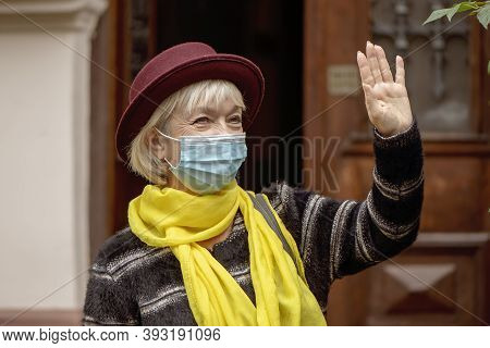 An Elderly Woman 60-65 Years Old In A Medical Mask Greets Someone By Raising Her Hand . Concept: Ret