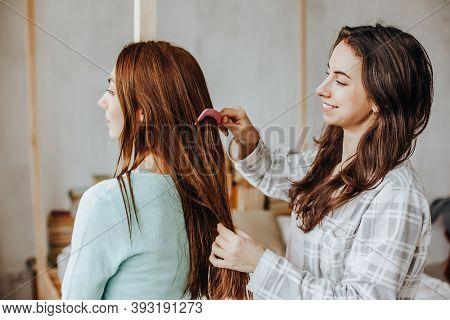 Two Girls Braid Their Hair At The Window. Woman Makes A Braid To Her Friend. Hair Weaving Hairstyles
