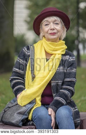 Street Portrait Of An Elderly Woman In A Fashionable Hat And Scarf Sitting On A Bench In The Park An