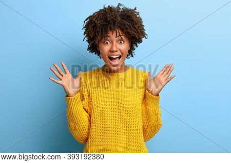 Photo Of Emotional Curly Haired Young Woman Exclaims With Joy, Raises Palms, Dressed In Yellow Sweat