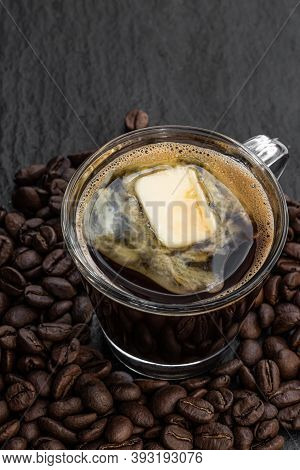 Small  Cup Of Fresh Fatty Coffee With Butter On Black Stone Background