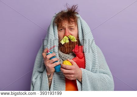 Photo Of Frustrated Ginger Man Treats Sore Throat With Aerosol, Holds Lemon, Hot Water Bottle, Wrapp