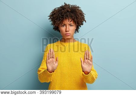 Serious Black Woman With Grumpy Expression Keeps Palms In Front, Makes Stop Gesture, Refuses Somethi