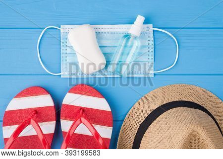 Vacation And Quarantine Concept. Top Above Overhead View Photo Of Soap Sanitizer Mask Flipflops And