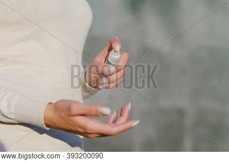 Girl Disinfects Her Hands With Antiseptic. Against The Background Of A Gray Concrete Wall.