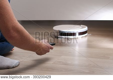 The Robot Vacuum Cleaner Cleans Under The Bed. High Quality Photo