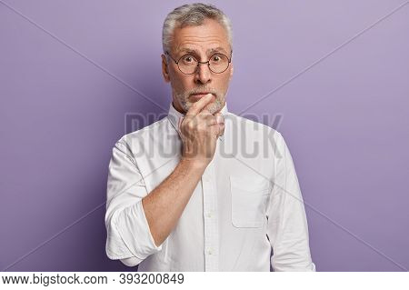 Isolated Shot Of Surprised Male Keeps Hand On Mouth, Dressed In Elegant Shirt, Poses Over Purple Bac