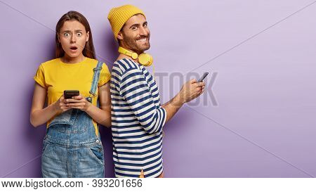 Photo Of Astonished Young Woman Wears Casual Yellow T Shirt And Denim Dungarees, Shocked Get Message