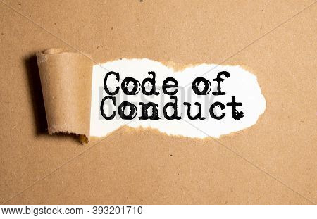 The Text Code Of Conduct Appearing Behind Torn Brown Paper.
