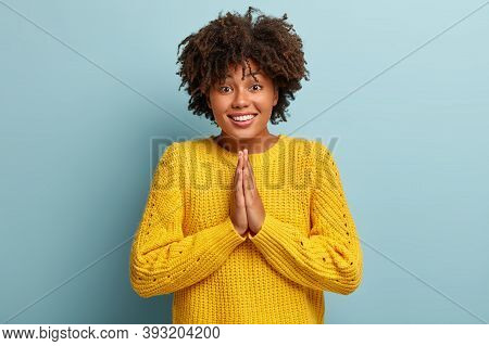 Do Me Favor. Cheerful Afro Girl Presses Palms In Pray Gesture, Asks For Help, Has Gentle Smile, Grin