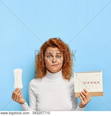Puzzled Ginger Woman Holds Sanitary Napkin And Menstruation Calendar With Marked Red Days, Suffers F