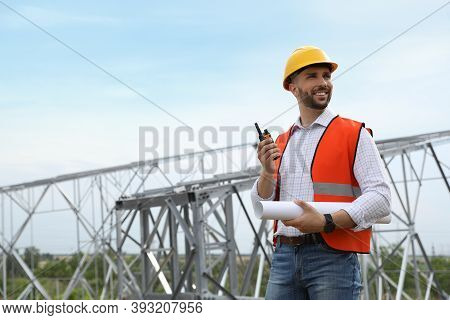 Professional Engineer With Plan And Walkie Talkie Near High Voltage Tower Construction Outdoors. Ins