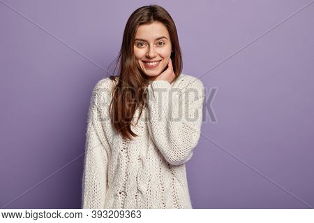 Half Length Shot Of Pretty Satisfied Woman With Gentle Smile, White Teeth, Looks Directly At Camera,
