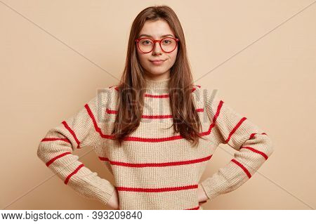 Self Assured Serious Lovely Woman Keeps Hands On Waist, Wears Red Rim Glasses And Striped Sweater, L