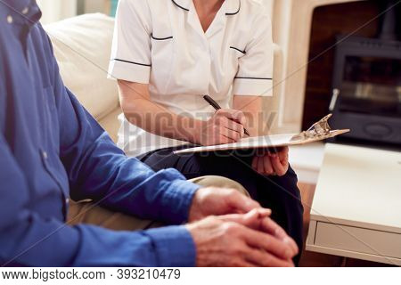 Close Up Of Female Doctor Making Notes During Home Visit To Senior Man For Medical Check