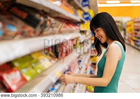 Side View Of Asian Woman Shopping In Grocery Store And Smiling, Buying Food, Standing In Supermarket