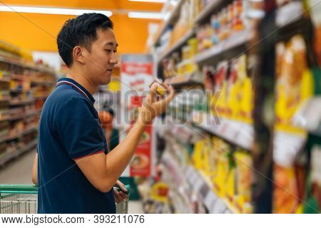 Side View Of Asian Man Shopping In Grocery Store, Buying Food, Standing In Supermarket Aisle Looking