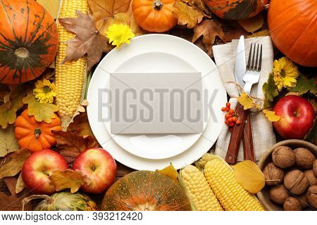 Table Setting Surrounded By Autumn Vegetables, Leaves And Flowers On Wooden Background, Flat Lay. Th