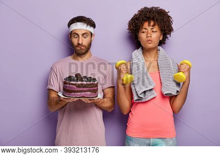 Serious Sporty Woman Trains With Dumbbells, Has Good Willpower, Looks At Baked Cake In Mans Hands, D