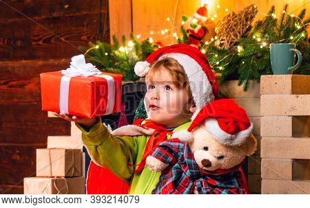 Baby Santa Boy Holding And Looking At Christmas Box Gift Trying To Guess What Is Inside It. Little K