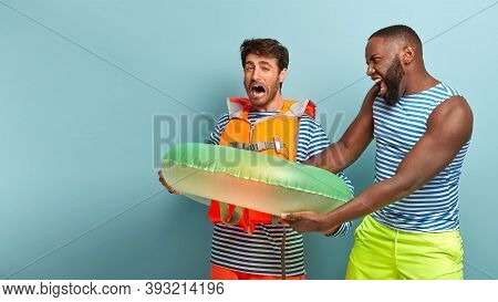 Greedy Man Doesnt Want To Share Swimring With Friend. Angry Dark Skinned Man Shouts Give Me Lifebuoy
