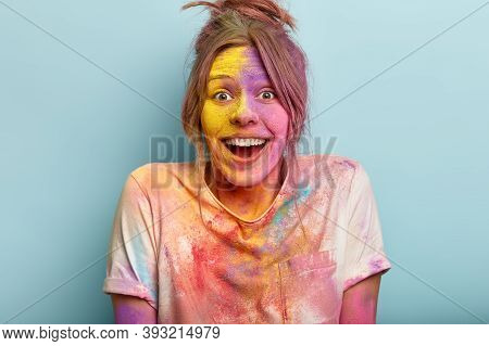 Headshot Of Optimistic Woman Plays With Colors On Holi Festival, Dressed In White T Shirt, Happy To