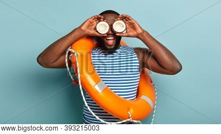 Funny Male Life Preserver Carries Two Coconuts Near Eyes, Wears Striped Vest, Lifebuoy With Rope On