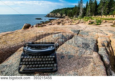 ACADIA NP, MAINE, USA - JULY 12, 2013: Antique Remington typewriter near ocean on granite rock with blue sky.