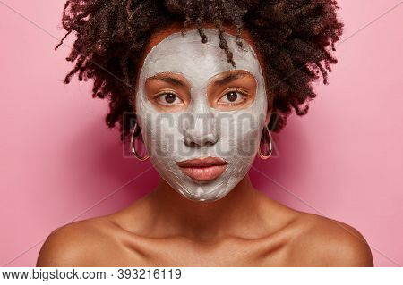 Close Up Shot Of Serious Woman Applies Clay Mask, Has Beauty Treatments, Uses Antiaging Procedures,