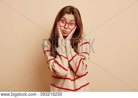 Displeased Young Caucasian Woman Keeps Hands On Cheeks, Blows Cheeks, Has Sullen Facial Expression,