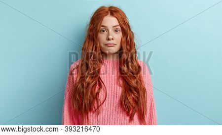 Headshot Of Confused Redhead Girl Purses Lower Lip, Has Surprised Look While Hears Something Puzzled