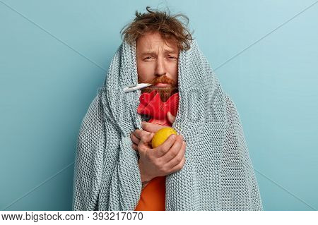 Photo Of Ill Bearded Man Wrapped In Coverlet, Hold Citrus And Hot Water Bottle, Measures Temperature