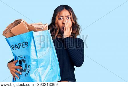 Young beautiful mixed race woman holding recycling wastebasket with paper and cardboard covering mouth with hand, shocked and afraid for mistake. surprised expression