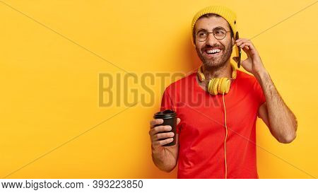 Indoor Shot Of Cheerful Millennial Man Speaks On Mobile Phone, Looks Away, Holds Takeout Coffee Make