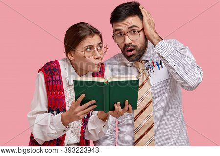 Puzzled Clumsy Female And Male Readers Look At Textbook, Have Worried Expressions, Cram Material, We