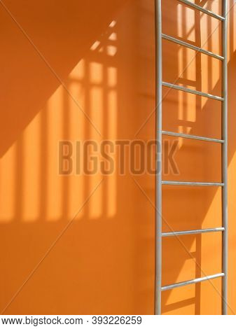 Sunlight And Shadow Of Balusters On Surface Of Fire Escape Outside Of Orange Building In Vertical Fr