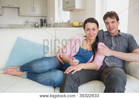 Young couple on the couch watching television in the living room
