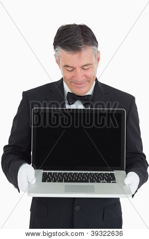 Happy waiter showing us something on a laptop in front of camera