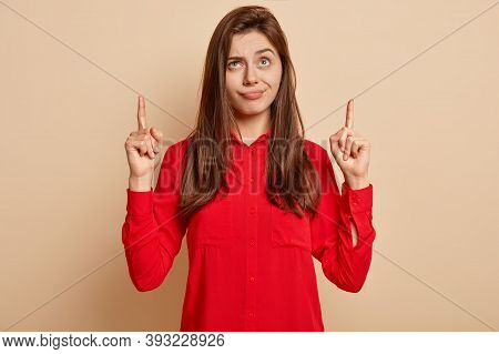 Horizontal Shot Of Dissatisfied Woman Purses Lips, Points Upwards, Tells About Something Unpleasant,