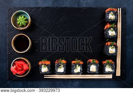 Set Of Traditional Japanese Food On A Dark Background. Sushi Rolls And Chopsticks For Sushi Top View