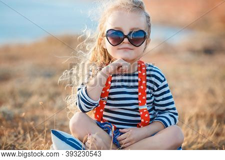 Happy Little Girl With Long Blond Hair In A Straw Hat And Sun Glasses Walks On A Meadow At Sunset Wi