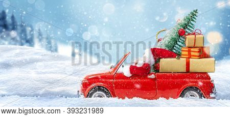 Santa Claus In Red Car Delivering Presents And Christmas Tree At Snowy Background. Christmas Or New